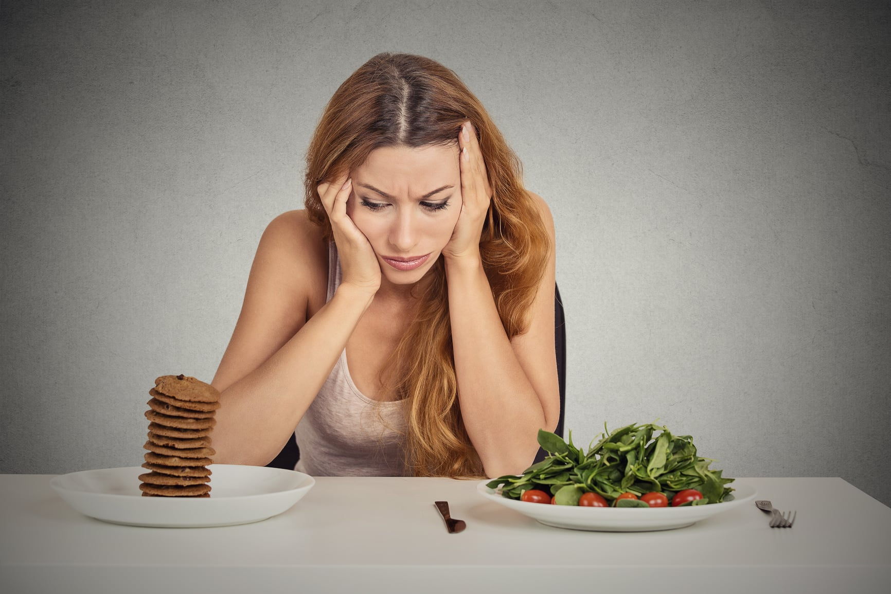 Young woman tired of diet restrictions deciding whether to eat healthy food or sweet cookies she is craving sitting at table isolated grey background. Human face expression emotion. Nutrition concept